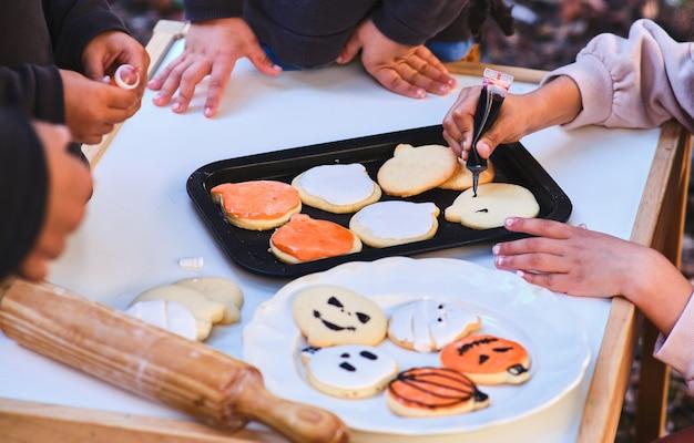 Kilka nierozpoznawalnych dzieci dekoruje ciasteczka na halloween