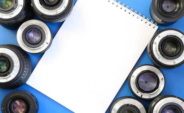 Kilka obiektywów fotograficznych i biały notatnik