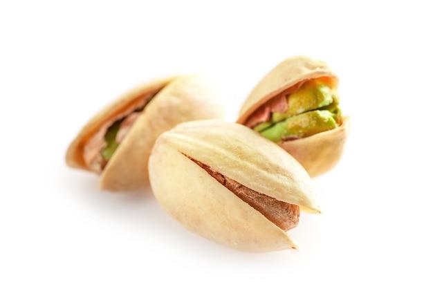 Kilka orzechów pistacjowych na białym tle