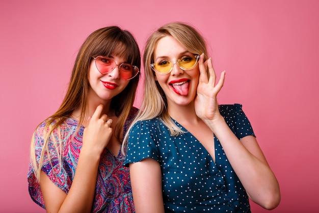 Kilka pięknych przyjaciółek, siostrzanych dziewczyn, które dobrze się bawią, ubrane w eleganckie letnie modne sukienki i okulary przeciwsłoneczne, pozują na różowej ścianie, przytulają się i uśmiechają, imprezując.