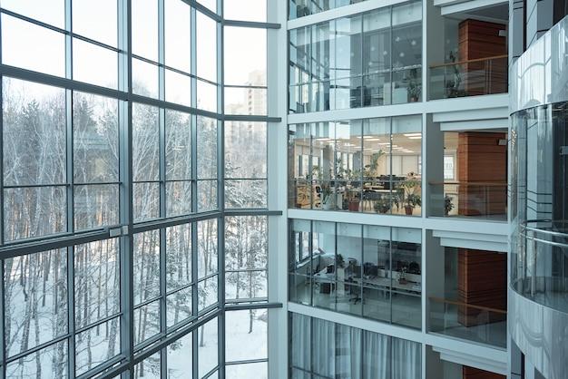 Kilka pięter dużego współczesnego centrum biznesowego z otwartymi biurami, oknami, balkonami i windą między nimi