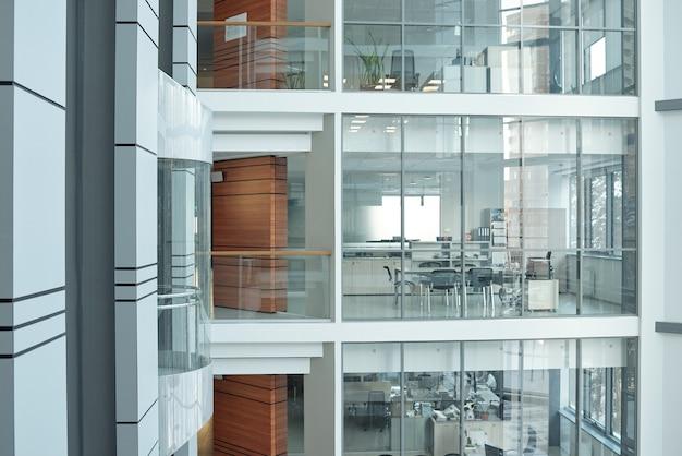 Kilka pięter w dużym, współczesnym centrum biznesowym z balkonami, oknami i otwartymi biurami z meblami