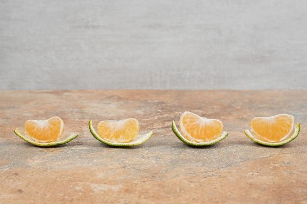 Kilka plasterków mandarynki na tle marmuru.