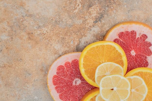 Kilka plasterków owoców cytrusowych na tle marmuru.
