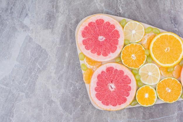 Kilka plasterków owoców i winogron na desce.