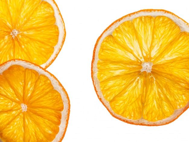 Kilka plasterków suszonej pomarańczy na białym tle.