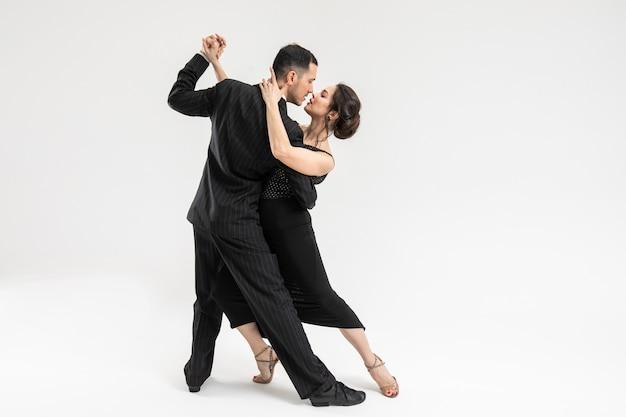 Kilka profesjonalnych tancerzy tanga w eleganckim garniturze i ubiorze stanowią w ruchu tanecznym. atrakcyjny taniec mężczyzny i kobiety patrząc oko w oko z miłością i pasją na białym tle.