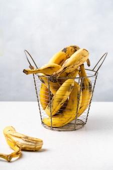 Kilka przejrzałych bananów w metalowym koszu.