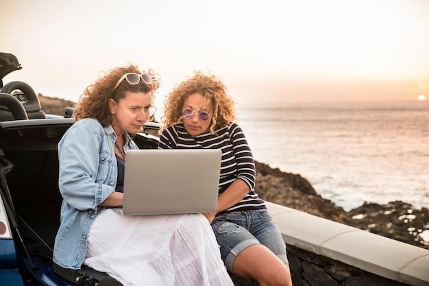 Kilka przyjaciółek korzysta razem z laptopa siedzącego z tyłu kabrioletu i zachodzącego słońca nad oceanem