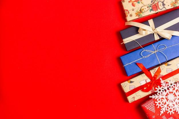 Kilka pudełek zawiniętych w papier prezentowy na czerwonym tle. widok z góry.