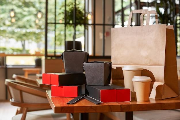 Kilka pustych jednorazowych pojemników na jedzenie na wynos, ułożone w papierowe torby i pudełka z miejscem na kopię logo marki. bliska strzał ekologicznego, aby przejść karton na stole w restauracji.
