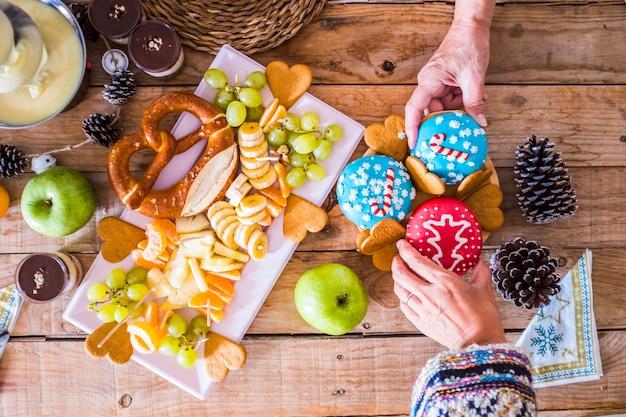 Kilka rąk w widoku z góry biorących dwa świąteczne słodkie ciasta na drewnianym stole z owocami i zimowymi dekoracjami