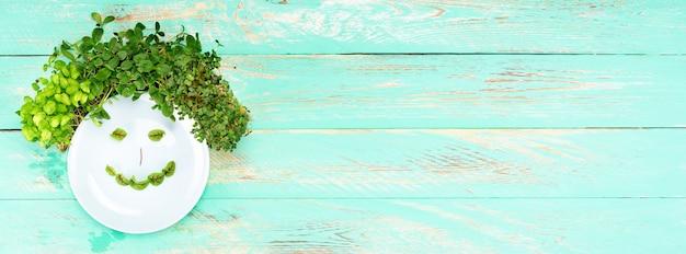 Kilka rodzajów microgreens na drewnianym tle. talerz z mikrozielonym uśmiechem. mikroziele różnych odmian na drewnianym tle