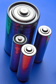 Kilka różnych baterii na niebieskim tle. zbliżenie.