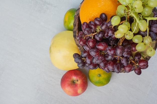Kilka różnych owoców w drewnianym wiaderku. zdjęcie wysokiej jakości