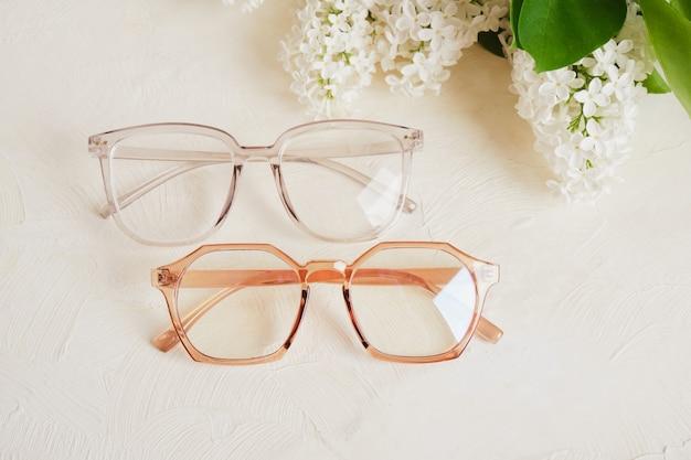 Kilka różnych trendów okularów i gałązki białego bzu na teksturowanym beżowym tle, okulary i kwiaty kopiują przestrzeń