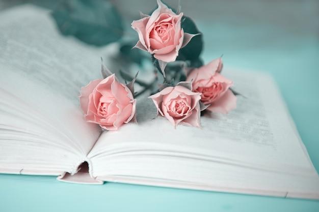 Kilka różowych róż na otwartej książce na zielonym stole