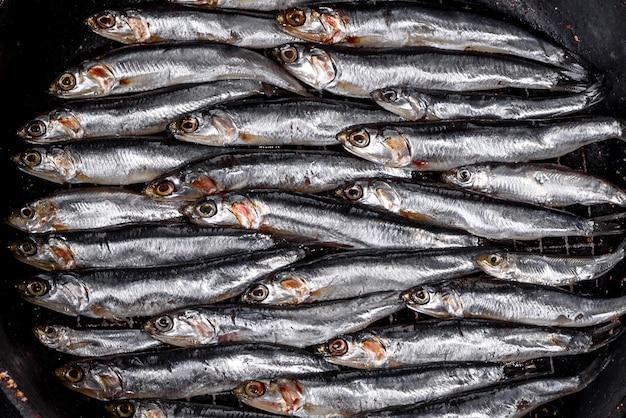 Kilka ryb solonych sardeli na ciemnym betonowym stole. koncepcja małych ryb