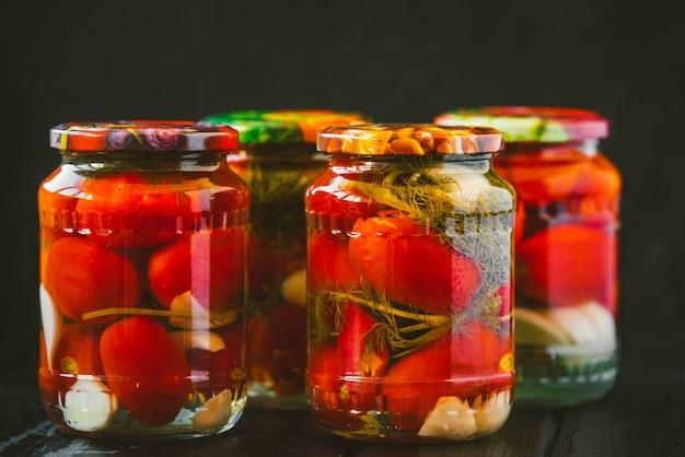 Kilka słoików konserwowych pomidorów z dojrzałymi pomidorami i czosnkiem.
