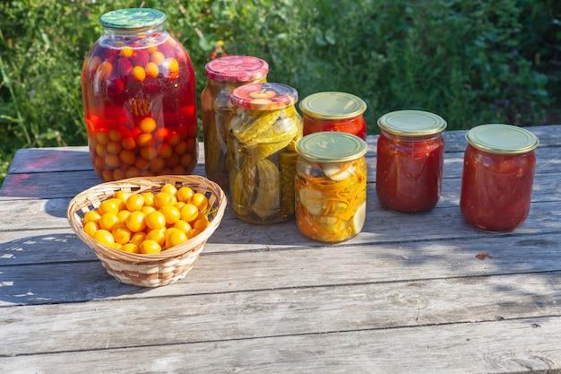 Kilka słoików marynat i sosu pomidorowego stoi na drewnianym stole. domowe przetwory na zimę