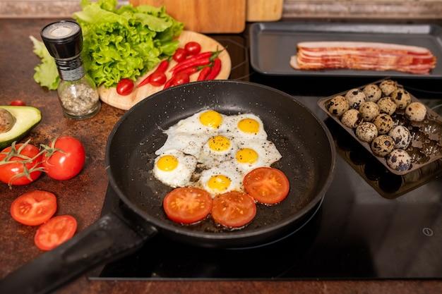 Kilka smażonych jaj przepiórczych i plasterków pomidora posypanych mielonym czarnym pieprzem na patelni w otoczeniu świeżych warzyw