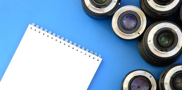 Kilka soczewek fotograficznych i biały notatnik leżą na jasnym niebieskim tle. miejsce na tekst