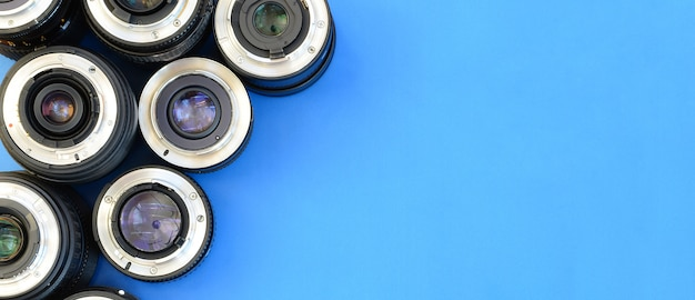 Kilka soczewek fotograficznych leży na jasnym niebieskim tle. miejsce na tekst