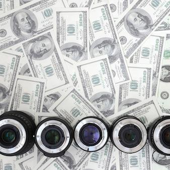Kilka soczewek fotograficznych leży na tle wielu banknotów dolarowych. miejsce na tekst