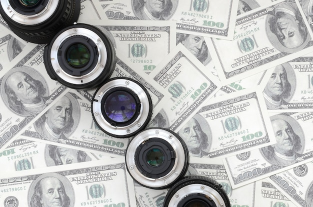 Kilka soczewek fotograficznych leży na tle wielu banknotów dolarowych.