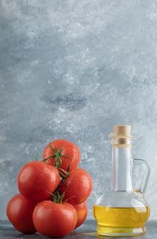 Kilka soczystych pomidorów ze szklaną butelką oleju.
