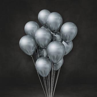 Kilka srebrnych balonów na tle czarnej ściany. renderowanie ilustracji 3d