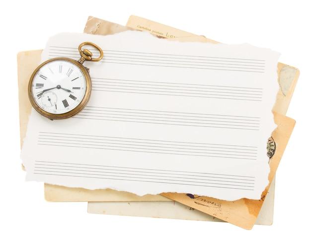 Kilka starych papierów do notatek z zabytkowym zegarem na białym tle
