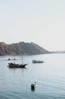 Kilka statków na wybrzeżu z widokiem na wzgórza