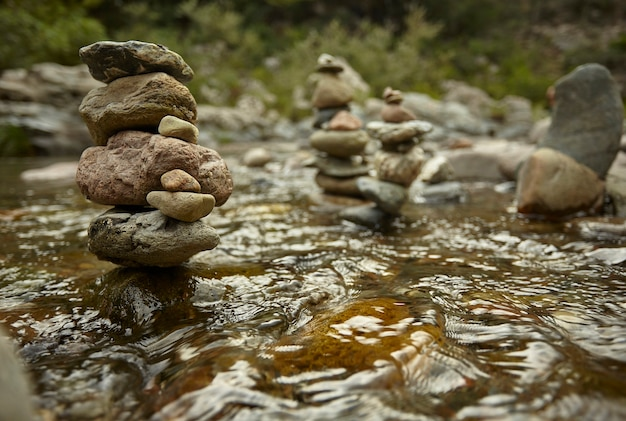 Kilka stosów kamieni przerywa przepływ wody w strumieniu.