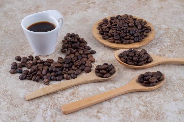 Kilka stosów ziaren kawy i filiżanka kawy