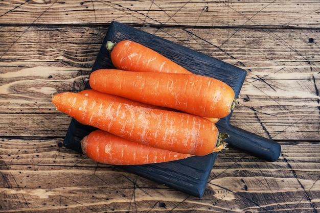 Kilka surowych marchewek na drewnianym tle rustykalnym.