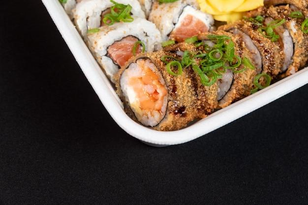 Kilka sushi w pojemniku styropianowym na czarnym tle