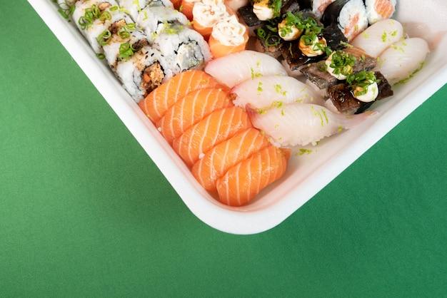 Kilka sushi w pojemniku styropianowym na zielonym tle