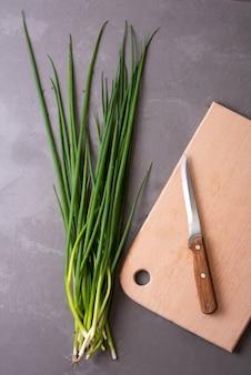 Kilka świeżej zielonej cebuli z deską do krojenia na szarym tle, zdrowa żywność, wegetarianizm, z bliska.