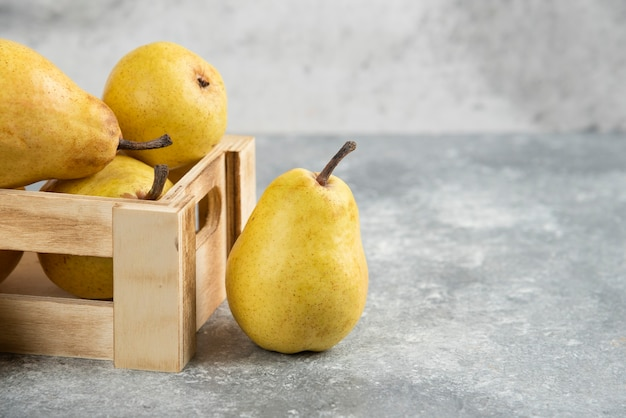 Kilka świeżych gruszek bio w drewnianym pudełku na marmurowej powierzchni.