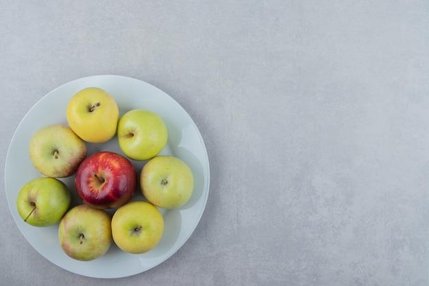 Kilka świeżych jabłek na białym talerzu.