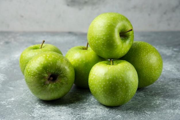Kilka świeżych jabłek na marmurze.