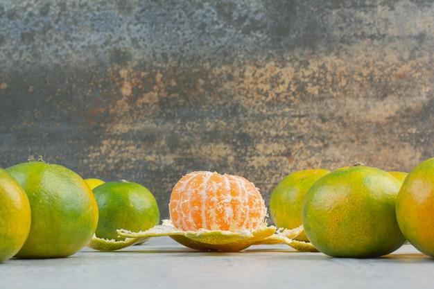 Kilka świeżych mandarynek na kamiennym stole. zdjęcie wysokiej jakości