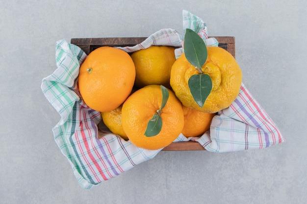 Kilka świeżych mandarynek w drewnianym pudełku.