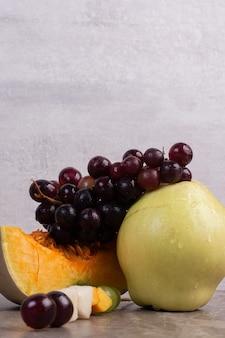 Kilka świeżych owoców na marmurowym stole.