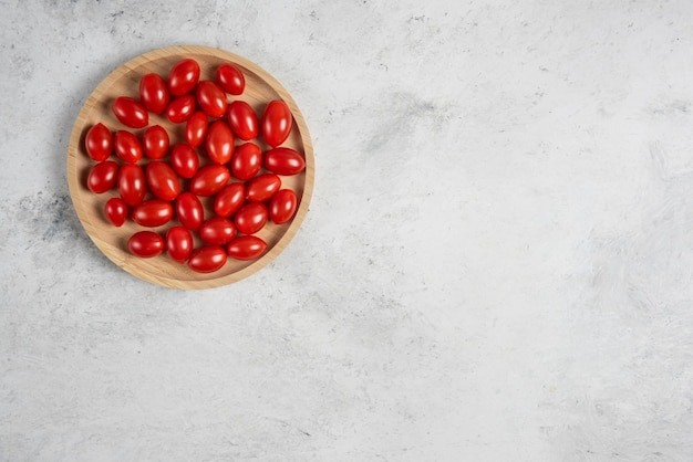 Kilka świeżych pomidorów na drewnianym talerzu.