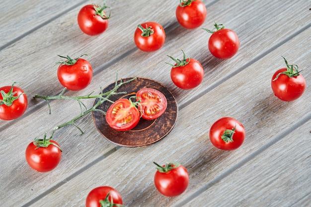 Kilka świeżych soczystych pomidorów i plasterków pomidora na drewnianym stole.