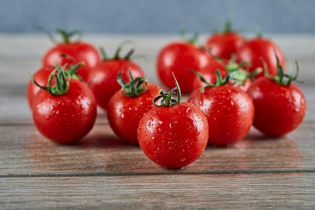 Kilka świeżych soczystych pomidorów na drewnianym stole.