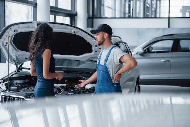 Kilka szczegółów dotyczących wypadku. kobieta w salonie samochodowym z pracownikiem w niebieskim mundurze, odbierając naprawiony samochód