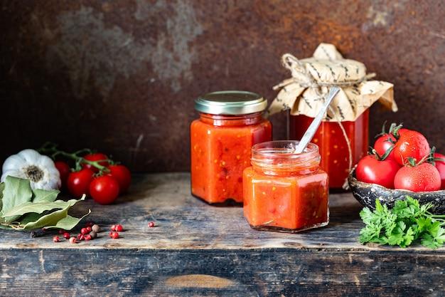 Kilka szklanych słoików z domowym sosem pomidorowym na bocznym drewnianym stole